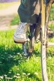 Espadrilles blanches sur des jambes du ` s de femme sur un vélo Photographie stock libre de droits