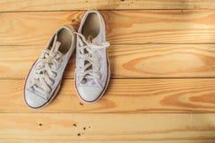 Espadrilles blanches sur des planchers en bois dur images stock