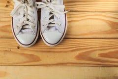 Espadrilles blanches sur des planchers en bois dur photos stock