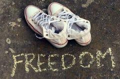 Espadrilles blanches sur l'asphalte Images libres de droits