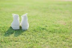 Espadrilles blanches sur l'herbe verte Photo stock