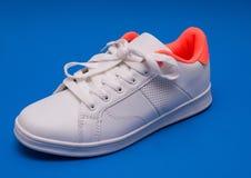 Espadrilles blanches sur le fond bleu sport de chaussures Images libres de droits