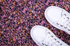 Espadrilles blanches sur le fond de tissu avec des fleurs Image libre de droits