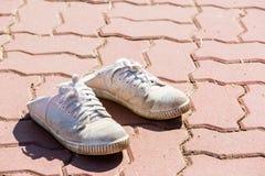Espadrilles blanches sur un plancher de brique Images stock