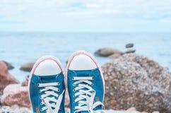 Espadrilles bleues élégantes sur un fond des roches dans la mer et le ciel Photo stock