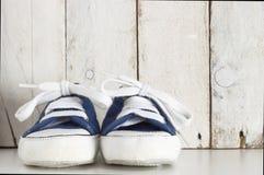 Espadrilles bleues d'enfant en bas âge sur un fond en bois blanc Images stock