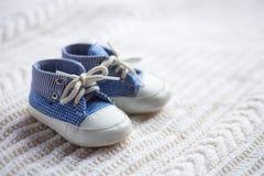 Espadrilles bleues de bébé garçon mignon sur le tissu tricoté blanc image libre de droits