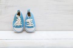 Espadrilles bleues de bébé garçon sur le fond en bois blanc Image libre de droits