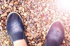 Espadrilles bleues de denim sur les pierres de mer Images stock