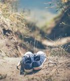 Espadrilles bleues de la jeunesse sur terre Photo stock