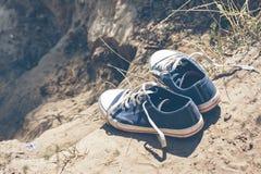 Espadrilles bleues de la jeunesse sur terre Photographie stock