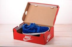 Espadrilles bleues de Nike pour courir dans la boîte rouge Photos libres de droits