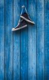 Espadrilles bleues de paires sur un mur en bois Image libre de droits