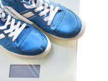 Espadrilles bleues du ` s d'hommes sur des échelles de place blanche sur la route goudronnée, automne Photos stock
