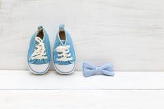 Espadrilles bleues du ` s de noeud papillon et d'enfants sur un backgroun en bois blanc Photos libres de droits
