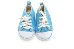 Espadrilles bleues pour l'enfant sur un fond blanc D'isolement Photos libres de droits