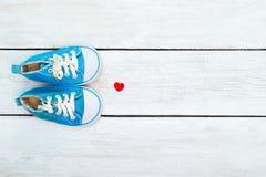Espadrilles bleues pour un garçon et un coeur rouge sur un backgr en bois blanc Photo stock