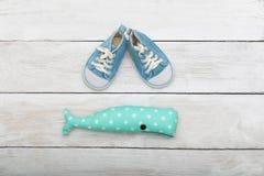 Espadrilles bleues pour un petit enfant et un jouet sur un fond en bois Photos stock