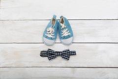 Espadrilles bleues pour un petit garçon et un noeud papillon sur un backgro en bois Photographie stock