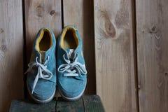 Espadrilles bleues se tenant sur les conseils en bois Images libres de droits