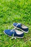 Espadrilles bleues sur l'herbe verte Photographie stock libre de droits