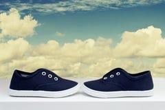 Espadrilles bleues sur le ciel nuageux de fond Photos libres de droits