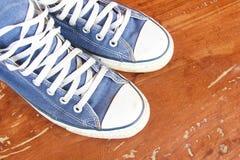 Espadrilles bleues sur le plancher en bois Images libres de droits
