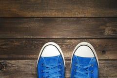 Espadrilles bleues sur le plancher en bois Photo stock