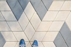 Espadrilles bleues sur le trottoir de bloc de béton Photos stock