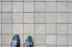 Espadrilles bleues sur le trottoir de bloc de béton Image stock