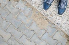 Espadrilles bleues sur le trottoir de bloc de béton Photo stock
