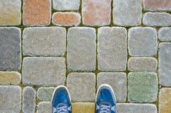 Espadrilles bleues sur le trottoir de bloc de béton Photographie stock libre de droits