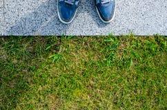 Espadrilles bleues sur le trottoir de granit près de la pelouse d'herbe Photographie stock libre de droits