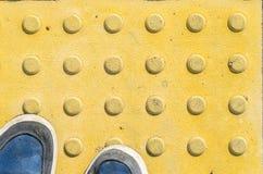 Espadrilles bleues sur les pavés tactiles jaunes Image libre de droits