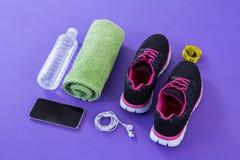 Espadrilles, bouteille d'eau, serviette, bande de mesure, téléphone portable et écouteurs Images libres de droits