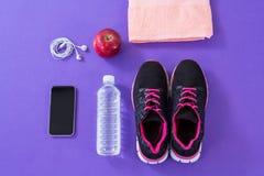 Espadrilles, bouteille d'eau, serviette, téléphone portable avec des écouteurs et pomme Photos libres de droits