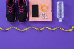 Espadrilles, bouteille d'eau, serviette, téléphone portable de mesure de bande avec des écouteurs et bande de forme physique Photos libres de droits