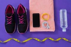 Espadrilles, bouteille d'eau, serviette, téléphone portable de mesure de bande avec des écouteurs et bande de forme physique Photographie stock