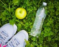 Espadrilles, bouteille de l'eau et pomme sur l'herbe verte fraîche Photo libre de droits