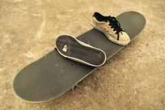 Espadrilles cassées sur une planche à roulettes Image libre de droits