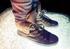 Espadrilles chaudes, chaussures sportives se tenant sur le verre criqué Photos libres de droits