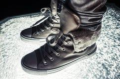 Espadrilles chaudes, chaussures sportives se tenant sur le verre criqué Images stock