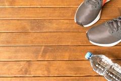 Espadrilles courantes, bouteille d'eau sur le fond en bois Avec vide Image libre de droits