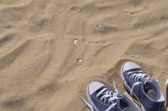 Espadrilles délacées par bleu sur la plage Photographie stock