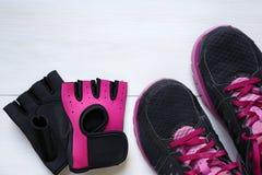 Espadrilles d'équipement de concept de forme physique et gants de séance d'entraînement Photographie stock libre de droits