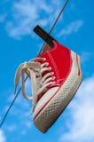 Espadrilles d'un rouge accrochant sur une corde à linge contre un ciel bleu Photo libre de droits