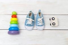 Espadrilles de bébé bleu et jouets en bois sur un fond en bois Image stock