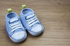 Espadrilles de bébé bleu sur une surface en bois Images libres de droits