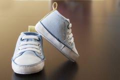 Espadrilles de bébé bleu sur une surface en bois Image libre de droits