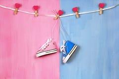 Espadrilles de bébé sur le fond rose et bleu, concept de fête de naissance Image libre de droits